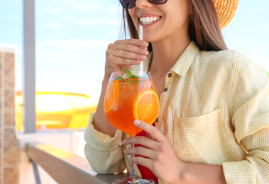 Woman with glass of refreshing drink outdoors, closeup
