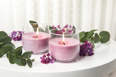 Burning candles in glass holders and flowers with leaves on white table