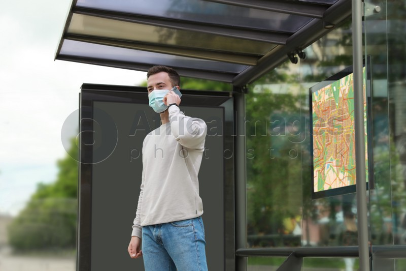 Young man in protective mask talking on phone while waiting for public transport at bus stop