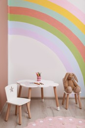 Cute children room interior with stylish furniture, toy bunny and rainbow art on wall