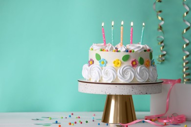 Delicious birthday cake and party decor on white wooden table against turquoise background, space for text