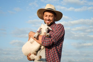 Farmer with cute goatling outdoors. Baby animal