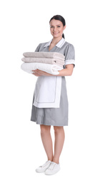 Young chambermaid holding stack of fresh towels on white background