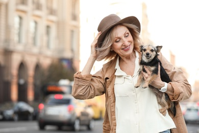 Beautiful mature woman with cute dog on city street