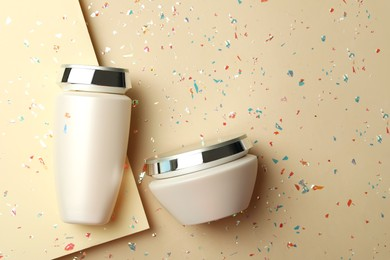 Hair care cosmetic products and confetti on color background, flat lay. Space for text
