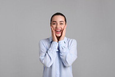 Portrait of happy young woman on light grey background. Personality concept