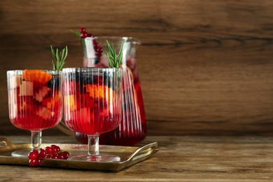 Glasses and jug of Red Sangria on wooden table. Space for text