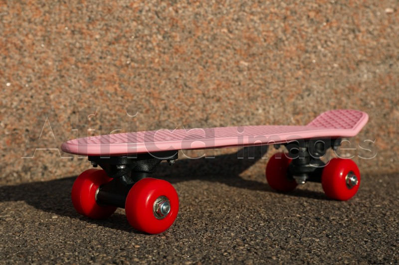 Pink skateboard with red wheels on asphalt outdoors