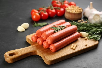 Fresh raw vegetarian sausages and vegetables on black table