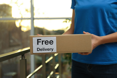 Courier holding parcel with sticker Free Delivery indoors, closeup