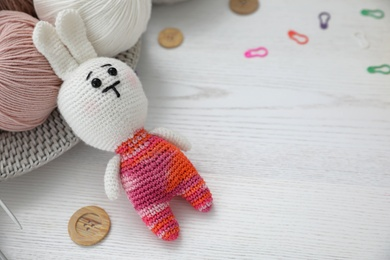 Crocheted bunny and threads on white wooden table. Engaging in hobby
