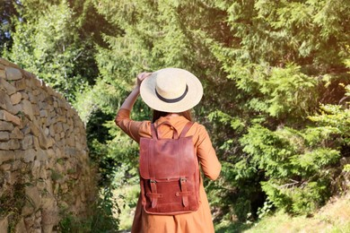 Woman with backpack and hat walking along stone wall in forest, back view