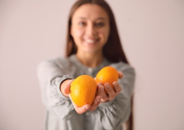 Woman with fresh tangerines on beige background, focus on fruits