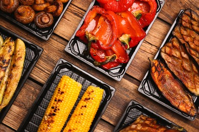 Plastic containers with different grilled meal on wooden table, flat lay. Food delivery service