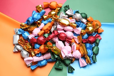 Many candies in different wrappers on color background, above view