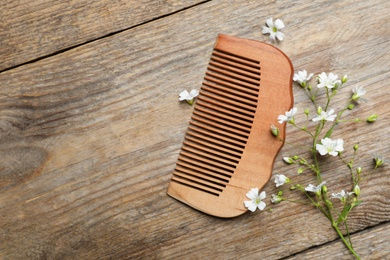 Comb and small white flowers on wooden background, flat lay. Space for text