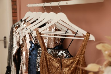Collection of trendy women's garments on rack indoors, closeup. Clothing rental service