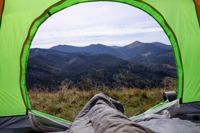 Grey sleeping bag in camping tent on hill, view from inside