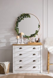 Modern room interior with chest of drawers and mirror on white wall