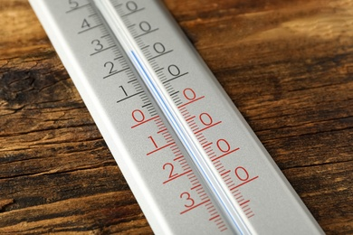 Modern weather thermometer on wooden background, closeup