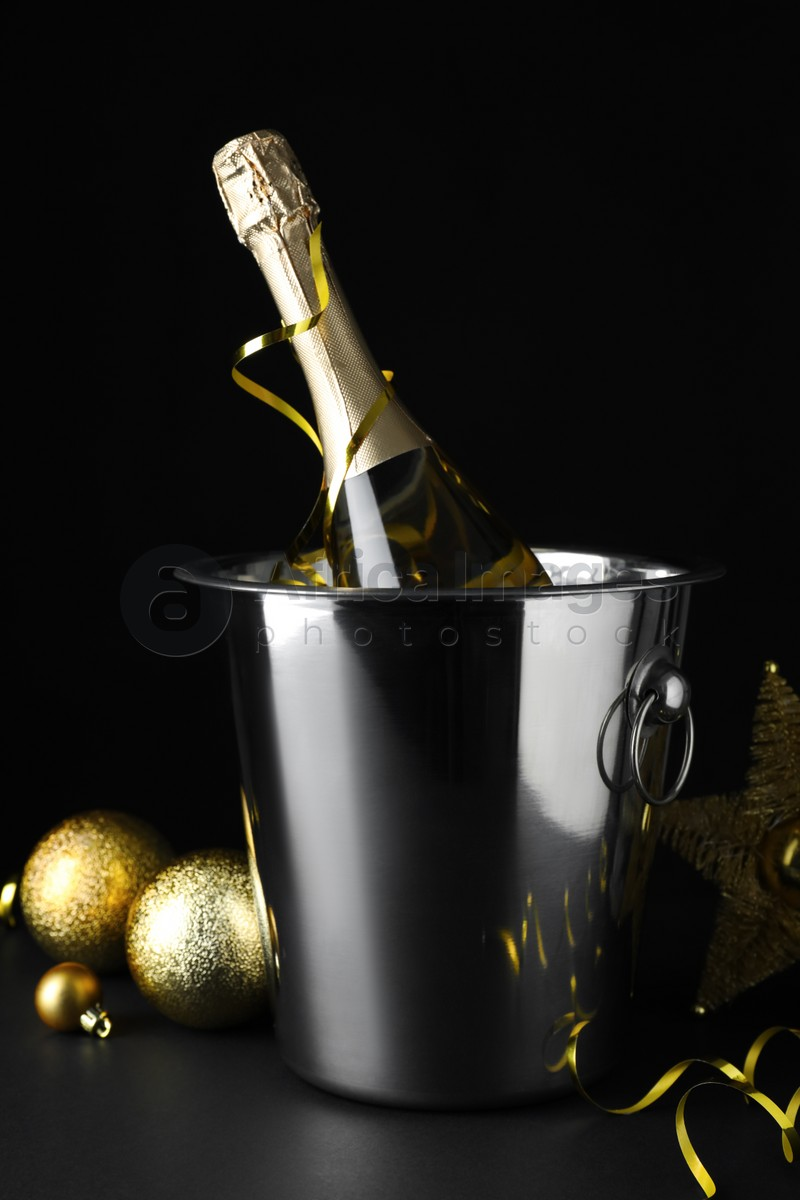 Happy New Year! Bottle of sparkling wine in bucket and festive decor on table against black background