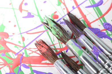 Brushes on canvas with colorful paint splashes, closeup. Art and creativity