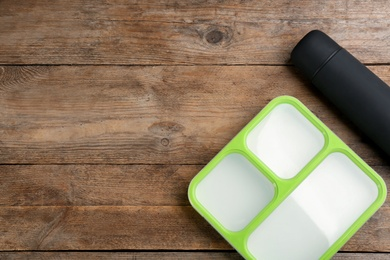 Thermos and lunch box on wooden table, flat lay. Space for text
