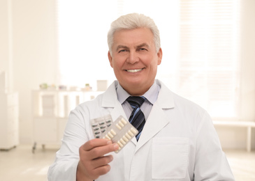 Portrait of senior pharmacist with pills in drugstore