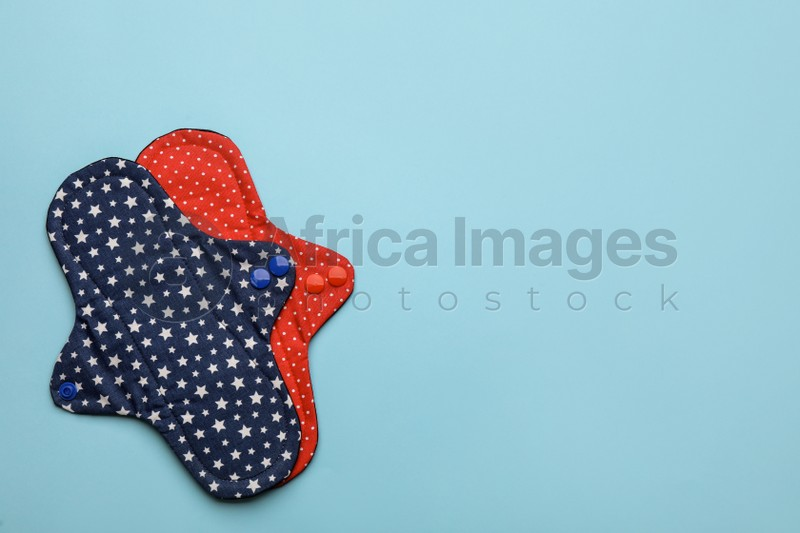 Reusable cloth menstrual pads on light blue background, flat lay. Space for text