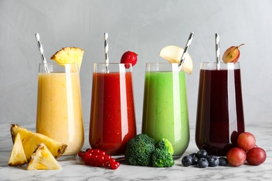 Glasses of delicious juices and fresh ingredients on white marble table