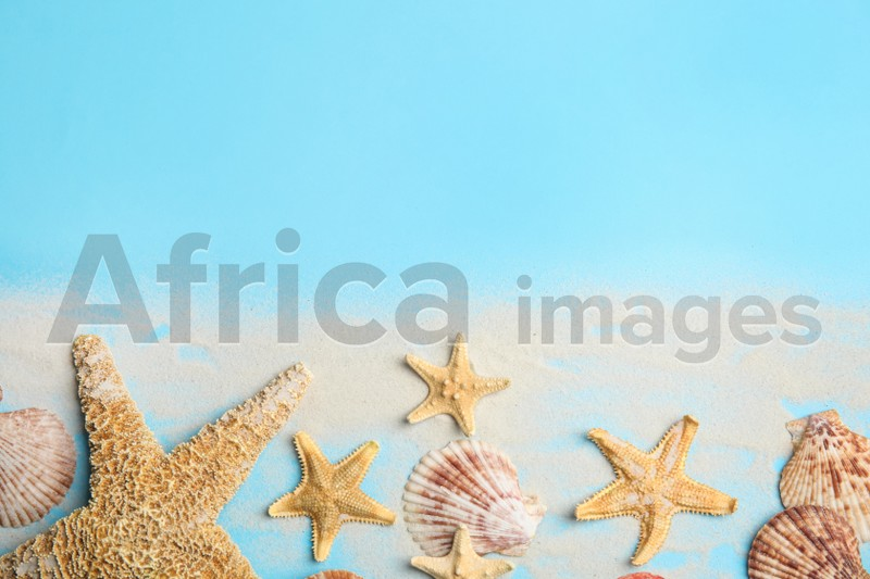 Beautiful sea stars, shells and sand on light blue background, flat lay. Space for text