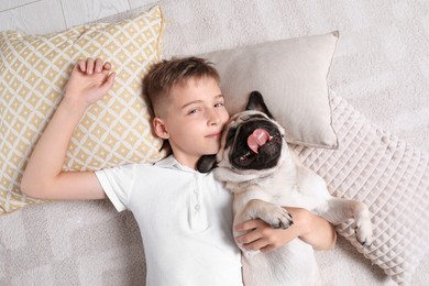 Boy with his cute pug lying on floor at home, top view