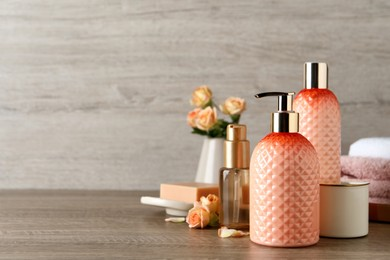 Stylish dispenser with liquid soap and other bathroom amenities on wooden table, space for text