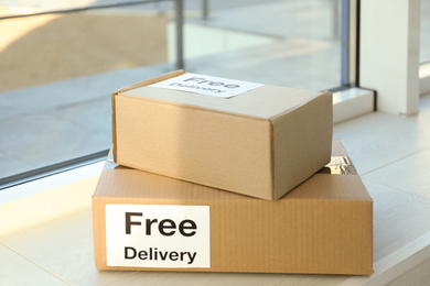 Parcels with sticker Free Delivery on window sill. Courier service