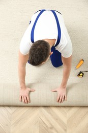 Worker rolling out new carpet flooring indoors, top view