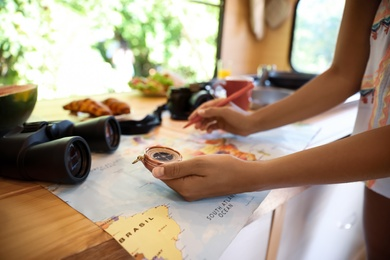 Young traveler with world map planning trip in motorhome, closeup