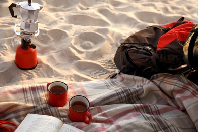 Cups of tea, book on blanket near camping stove with moka pot and backpack at sandy beach