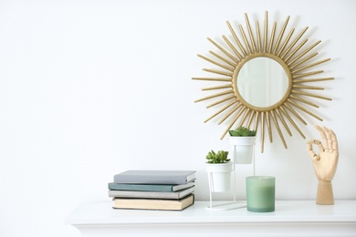 Burning candle, books and plants on shelf indoors, space for text. Interior elements