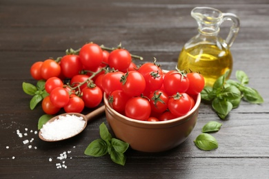 Fresh cherry tomatoes, basil and sea salt on wooden table