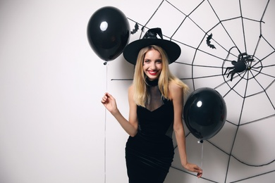 Woman in witch hat with balloons posing near white wall decorated for Halloween