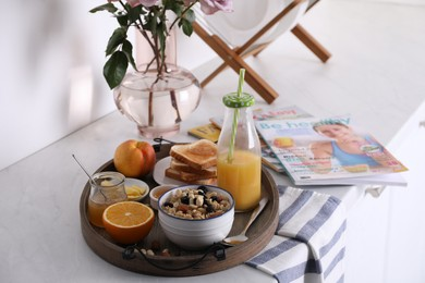 Tray with tasty breakfast on white table. Space for text