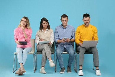 People waiting for job interview on light blue background