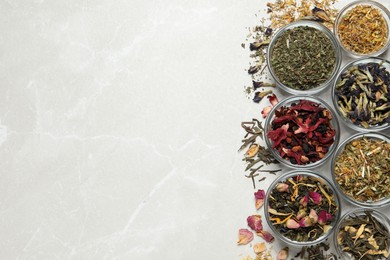 Flat lay composition with different dry teas on light table, space for text
