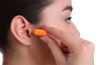 Young woman inserting foam ear plug on white background, closeup