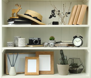 White shelving unit with photo frames and different decorative elements