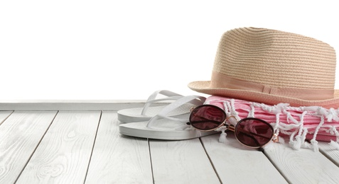 Hat, shoes, sunglasses and blanket on white wooden table, space for text. Beach accessories