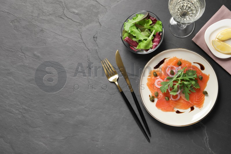 Delicious salmon carpaccio served on black table, flat lay. Space for text