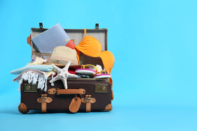 Packed vintage suitcase with different beach objects on light blue background, space for text. Summer vacation