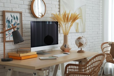 Stylish home office interior with comfortable workplace near white brick wall