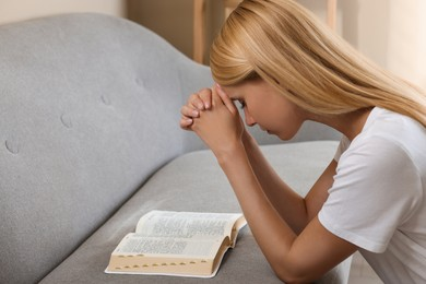 Religious young woman with Bible praying indoors